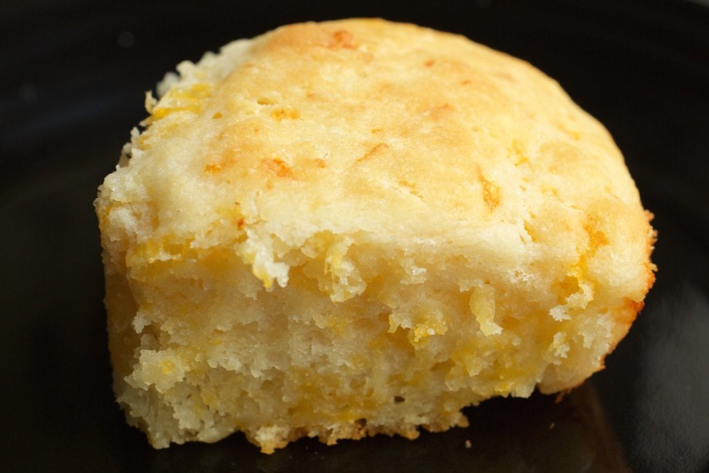 A thick cheesy buttermilk biscuit on a black background