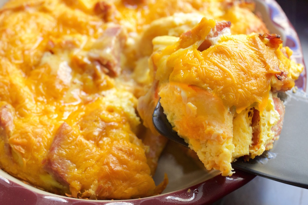 A spatula holds up a piece of ham and croissant breakfast casserole with the casserole dish in the background