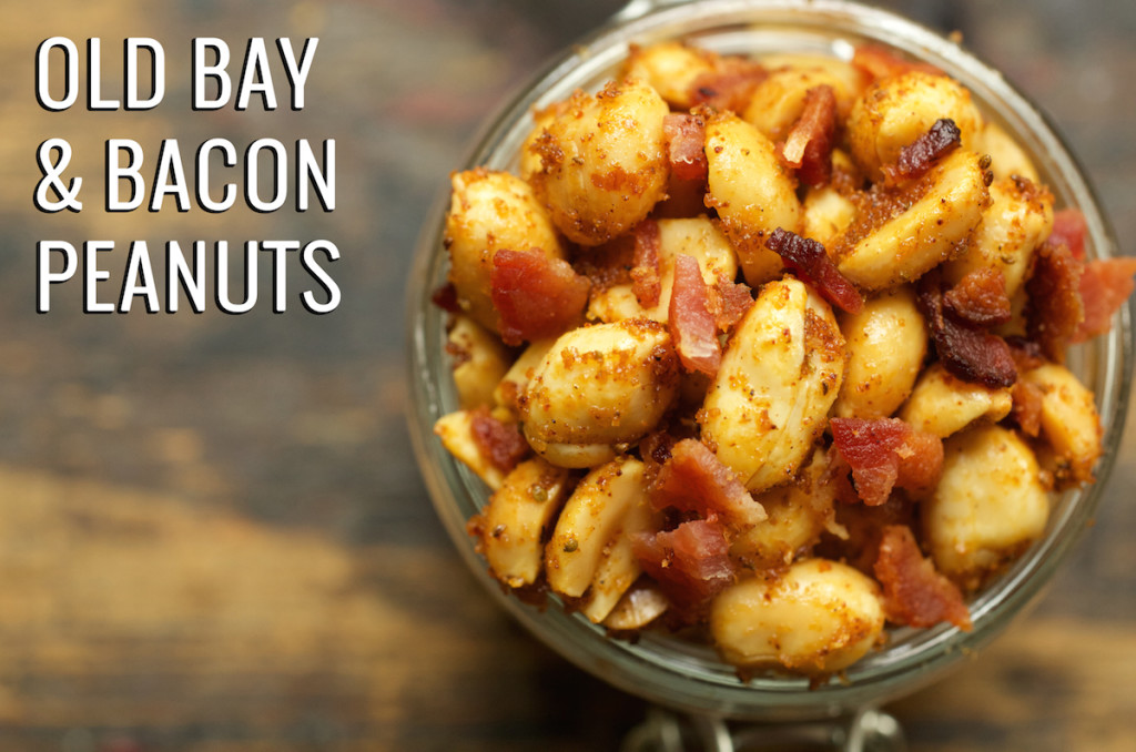"""Overhead look at a glass jar filled to the top with Old Bay & bacon peanuts. Text in the upper left corner reads """"Old Bay & Bacon Peanuts""""."""