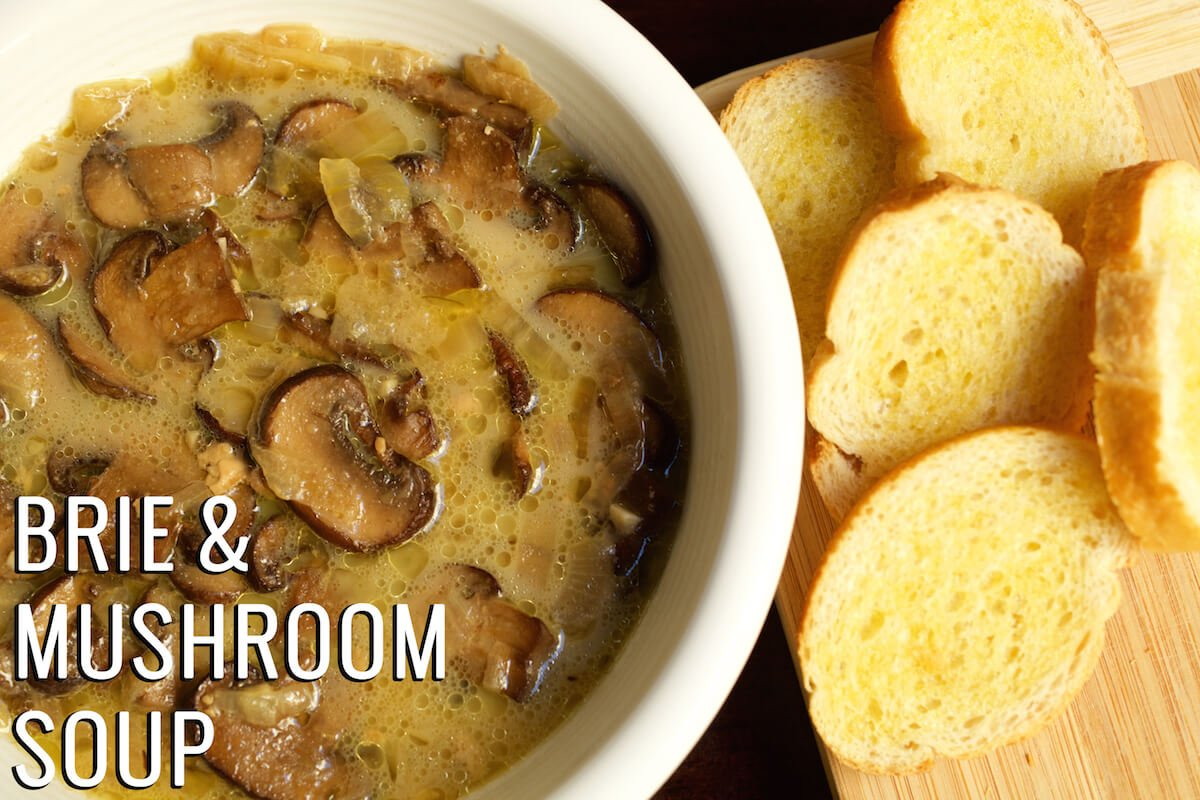 """Mushroom soup in a white bowl next to a cutting board with sliced baguette. Text in the left hand corner reads """"Brie & Mushroom Soup""""."""