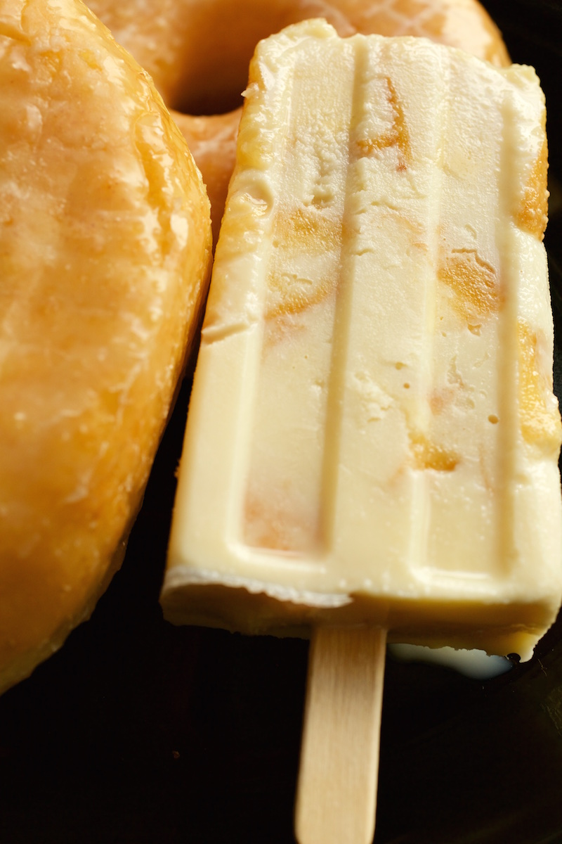 Close up of a Donuts & Milk Popsicle on a dark background.