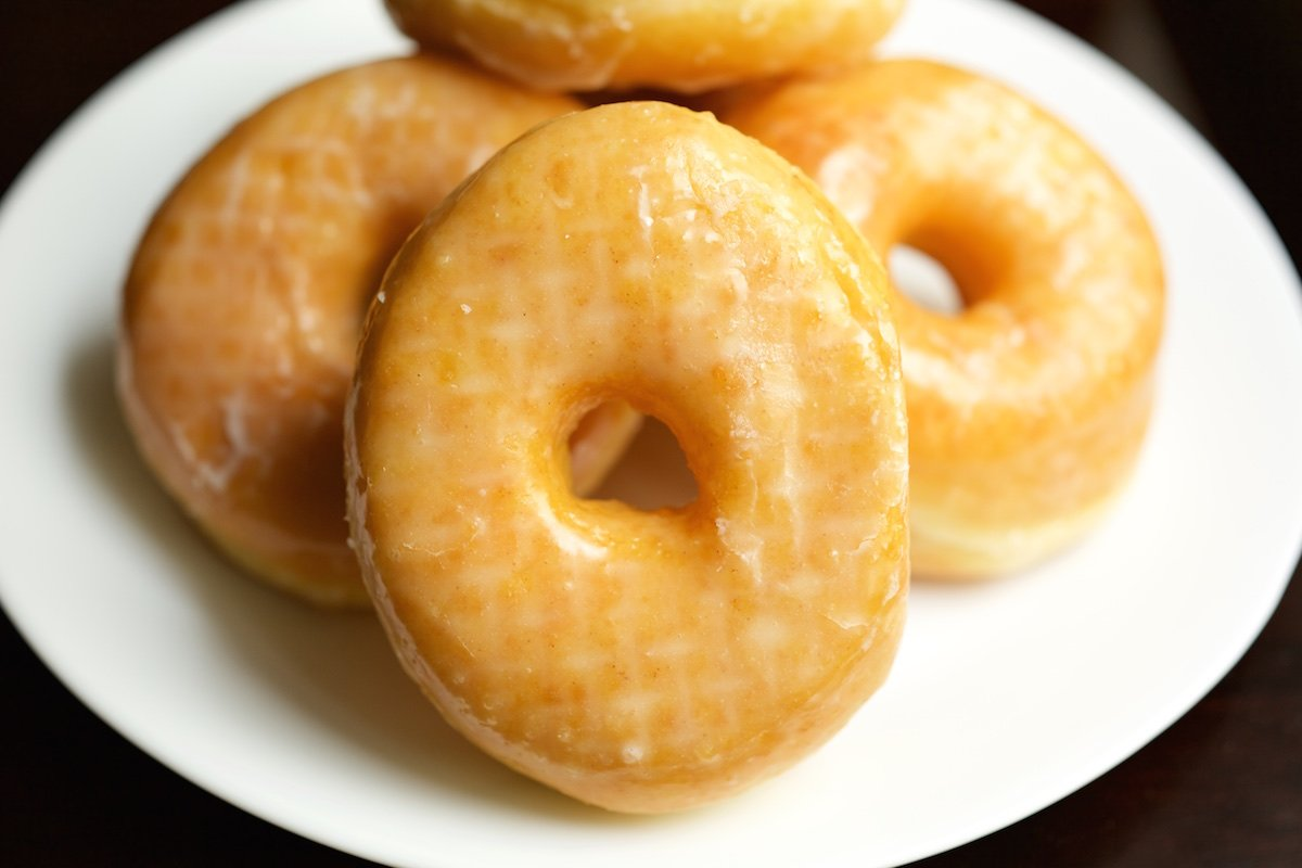 5 glazed donuts sit on a white plate.