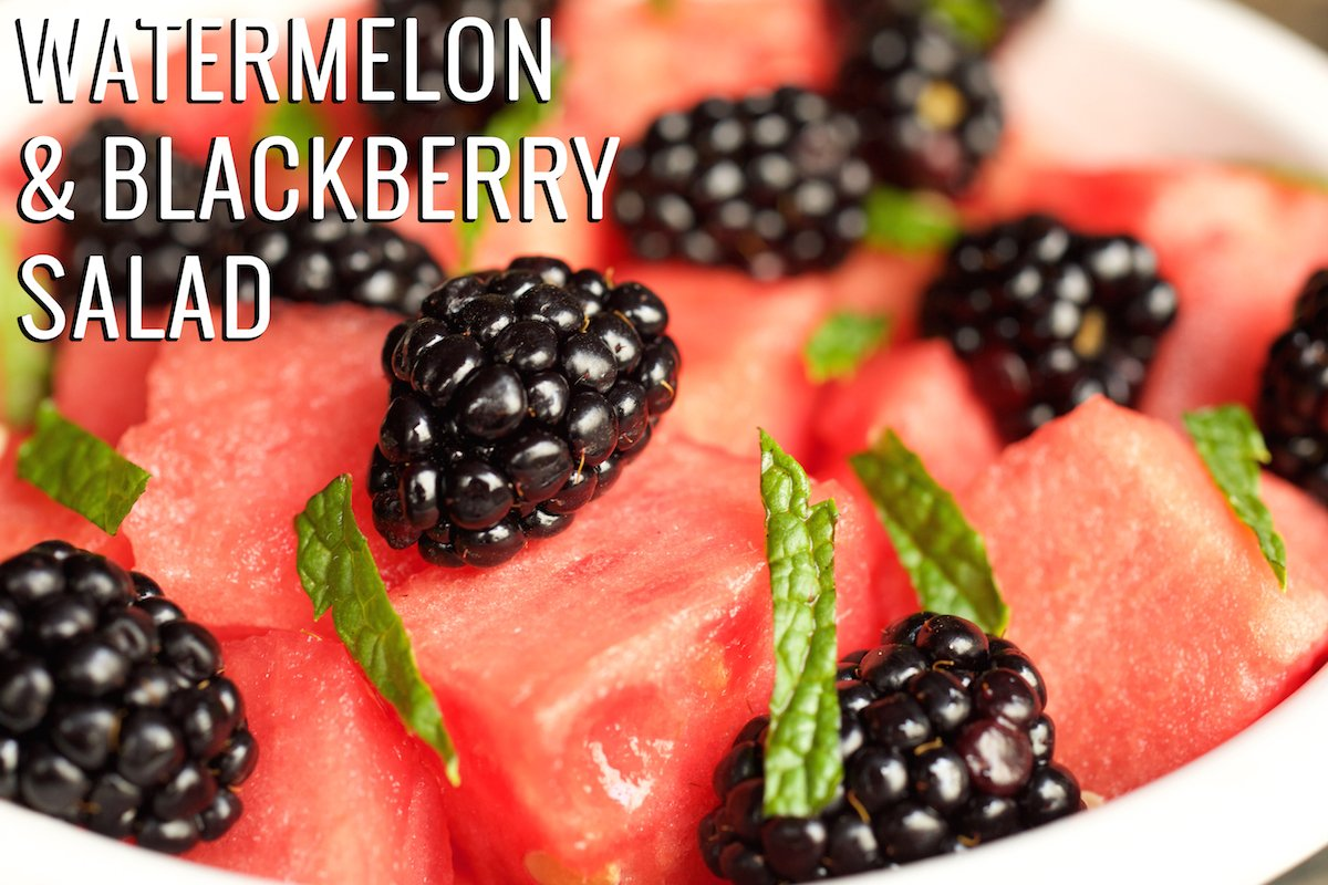 """A close up of a bowl with cut watermelon, whole blackberries, and chopped mint. Text in the upper left hand corner reads """"Watermelon & Blackberry Fruit Salad"""""""