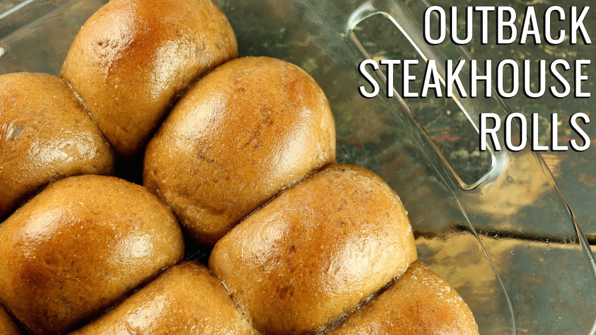 """Close up of brown rolls in a glass casserole dish. Text reads """"Outback Steakhouse Rolls"""""""