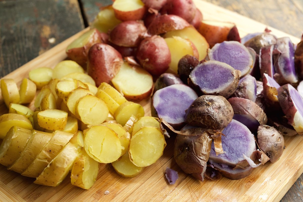 A cutting board with sliced yellow potatoes, sliced red potatoes, and sliced purple potatoes.
