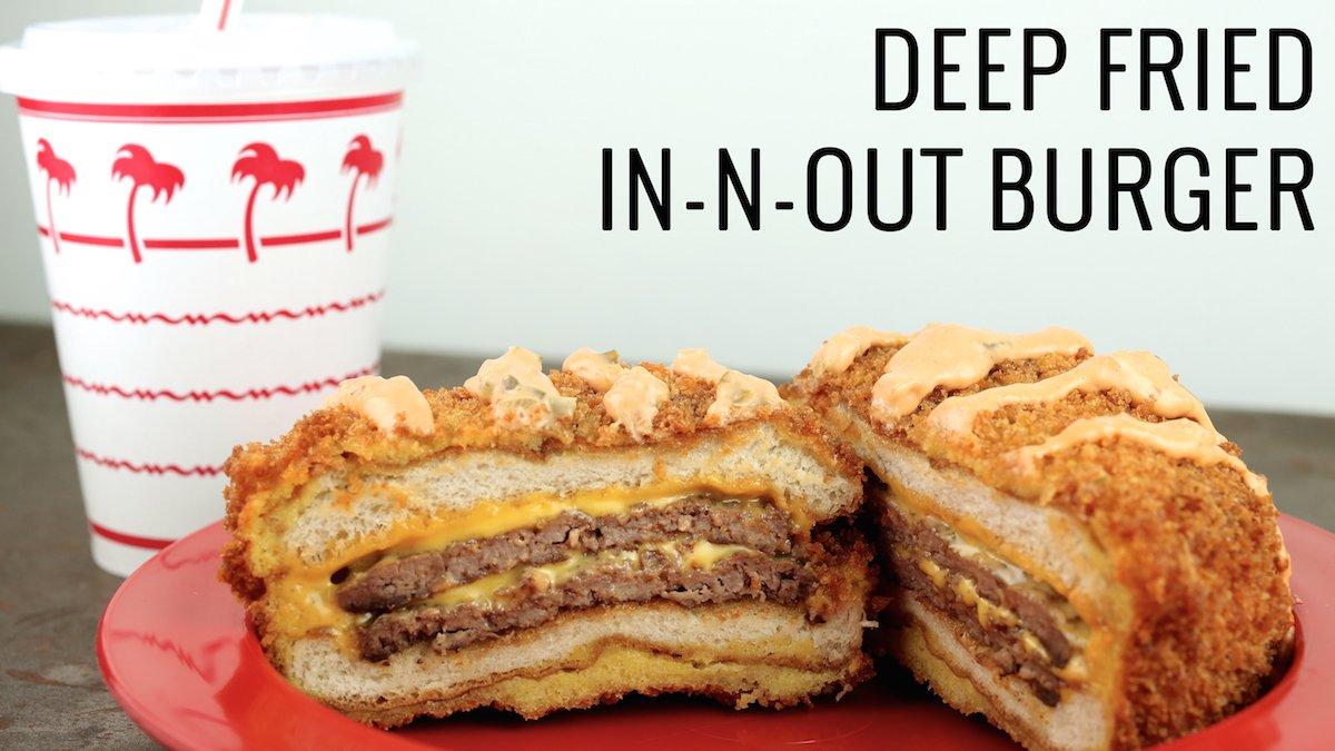 A deep-fried In-N-Out cheese burger sits on a red plate in front of the classic palm tree In-N-Out soda cup.