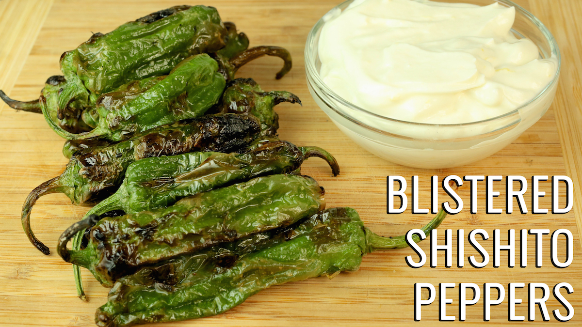 Blistered Shishito Peppers on a cutting board next to a small bowl lemon whipped goat cheese.