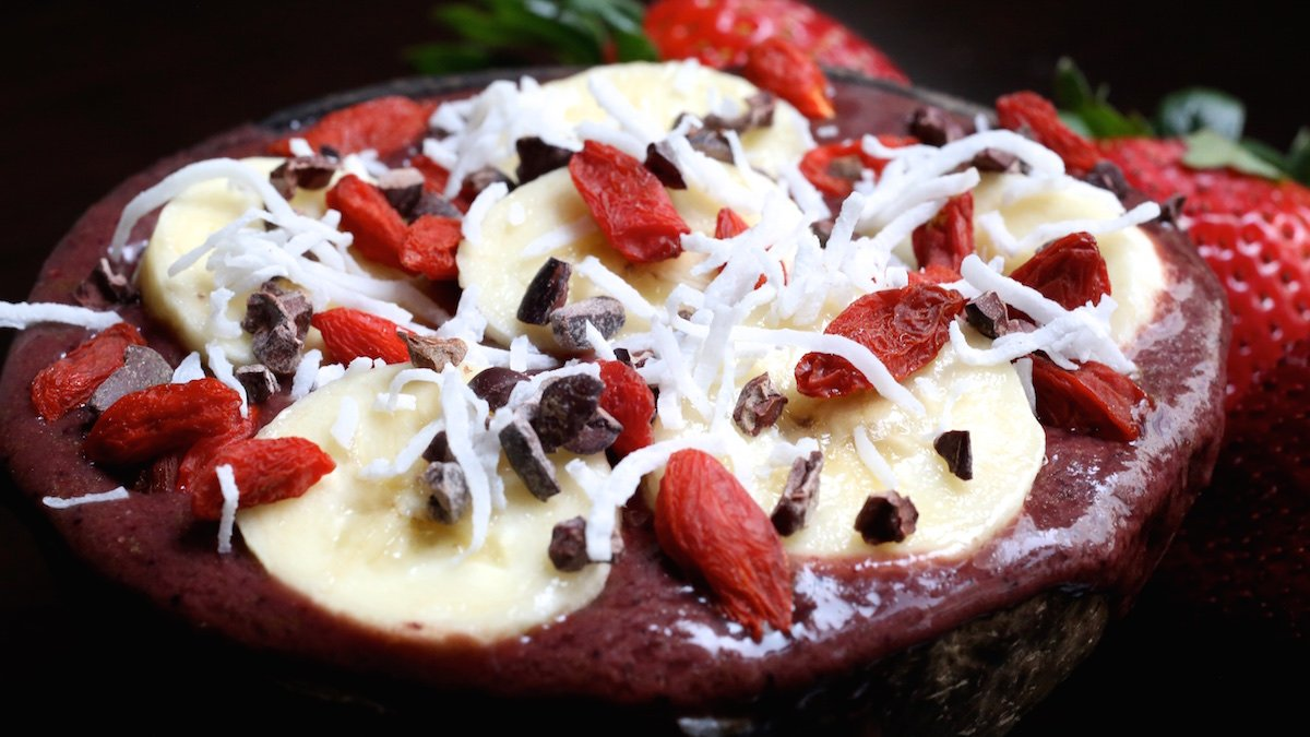 A side view of a coconut shell bowl filled with acai and topped with sliced banana, goji berries, cacao nibs, and shredded coconut.