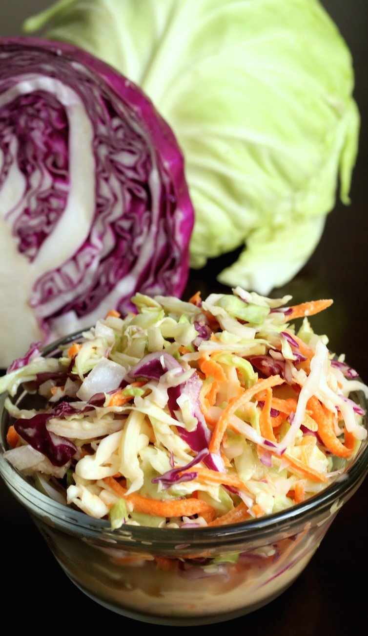 A small glass bowl of copycat KFC coleslaw sits in front of a cabbage head sliced in half.