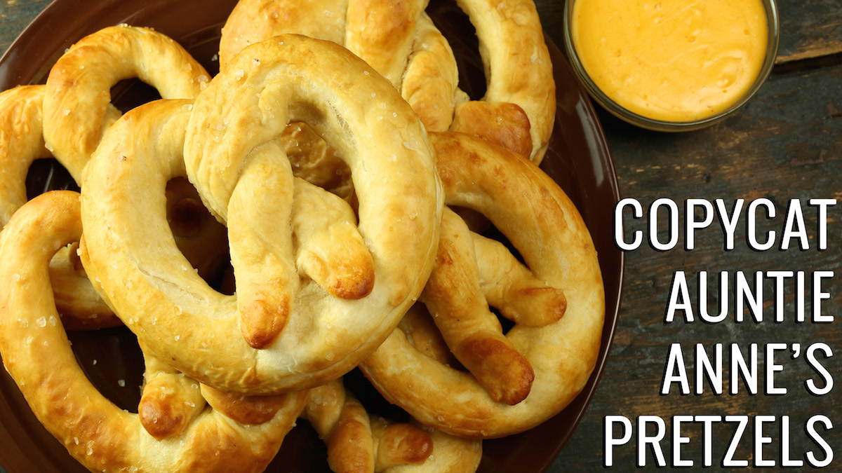 """Homemade pretzels sitting on a brown plate next to a small bowl of cheese sauce. Text reads """"Copycat Auntie Anne's Pretzels Recipe"""""""