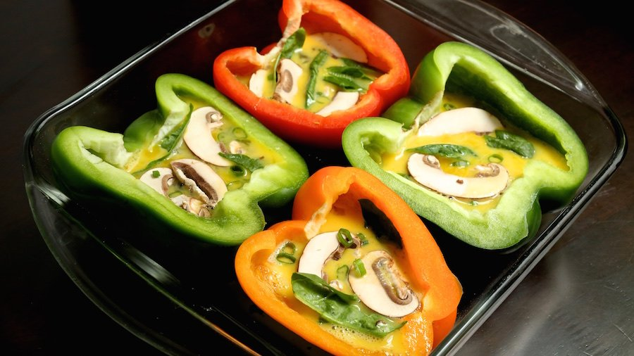 4 bell pepper halves with raw scrambled egg, sliced mushrooms, and spinach in a glass baking pan.