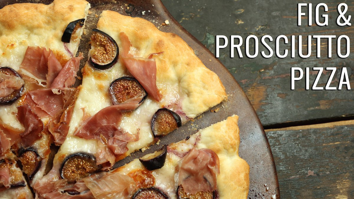 """A sliced pizza sits on a pizza stone. Text reads """"Fig and Prosciutto Pizza"""""""