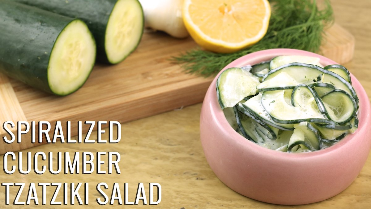 A pink bowl of Spiralized Cucumber Tzatziki Salad next to sliced cucumbers, lemon, dill, and garlic on a cutting board.