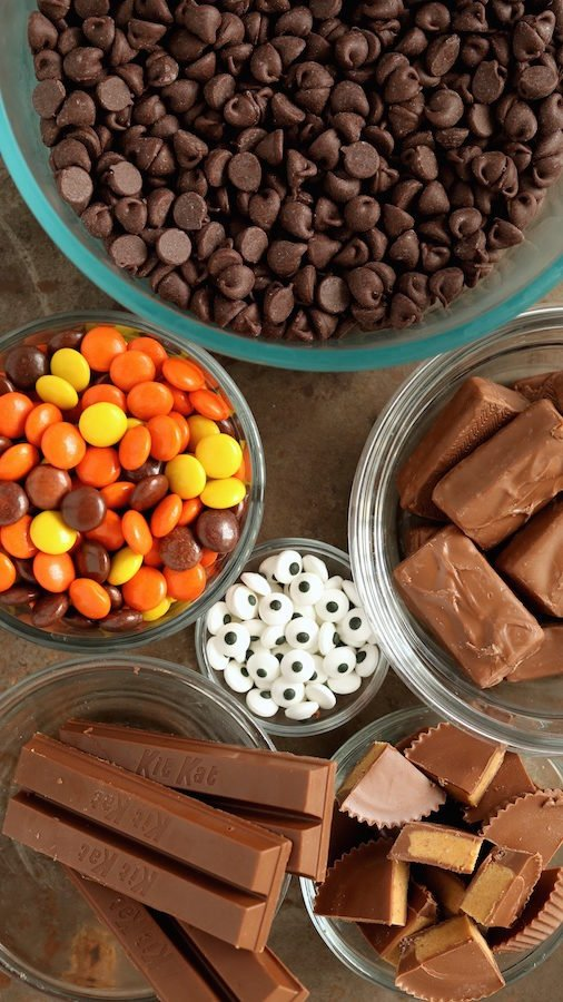 Overhead view of Halloween candy bark ingredients - mini chocolate chips, Reese's pieces, edible candy eyes, kit kats, chopped Reese's cups and mini candy bars.