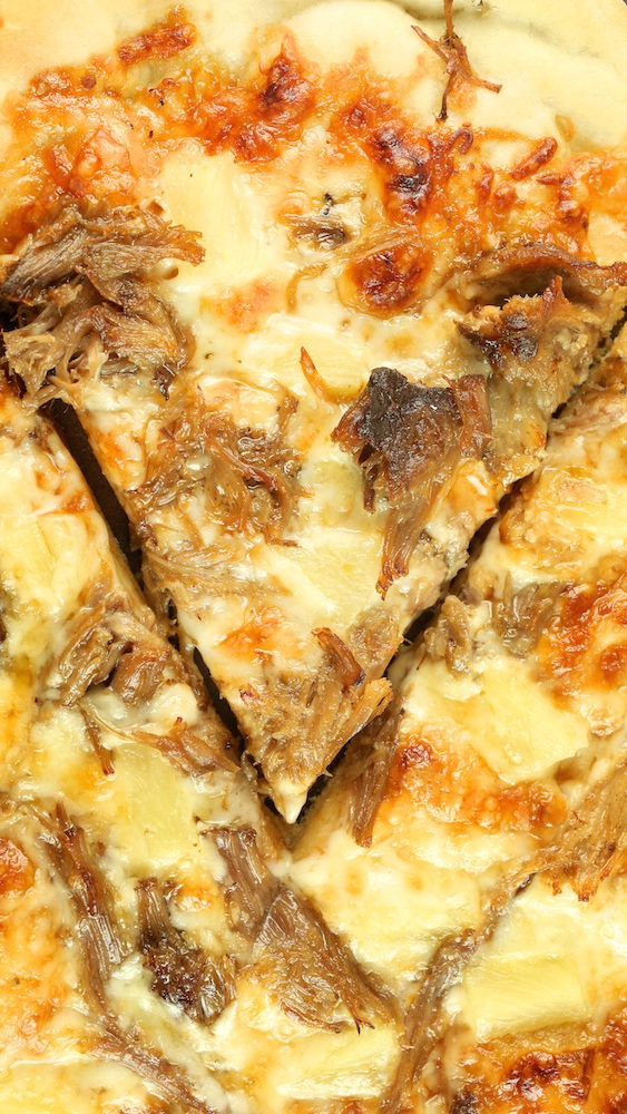 A slice of Kalua pork pizza with pineapple has been cut