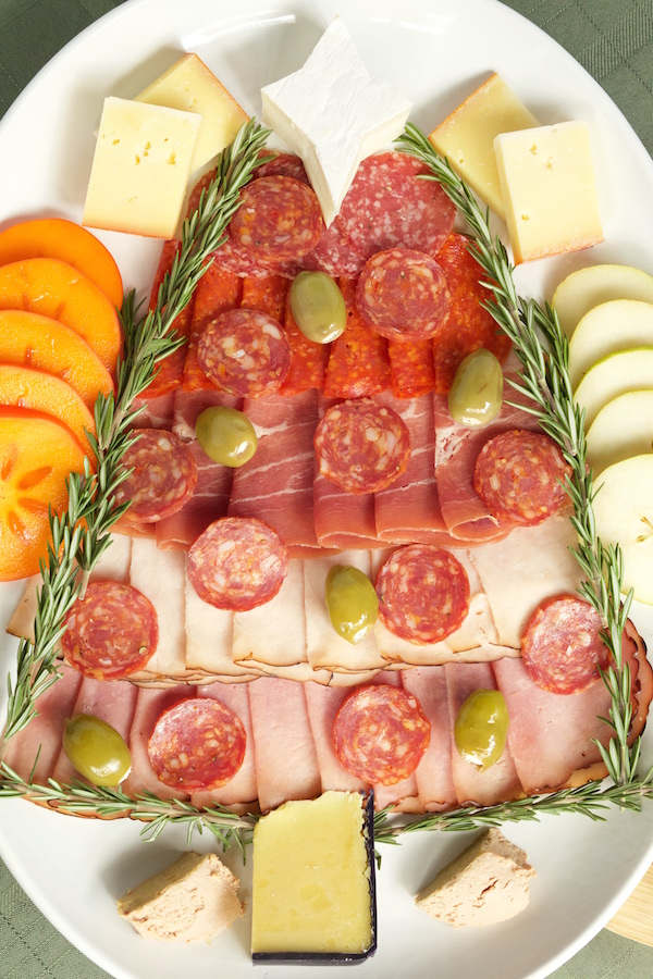 Christmas Tree Charcuterie Tray with assorted meats and cheeses, fresh persimmon and pear, and duck foie gras mousse