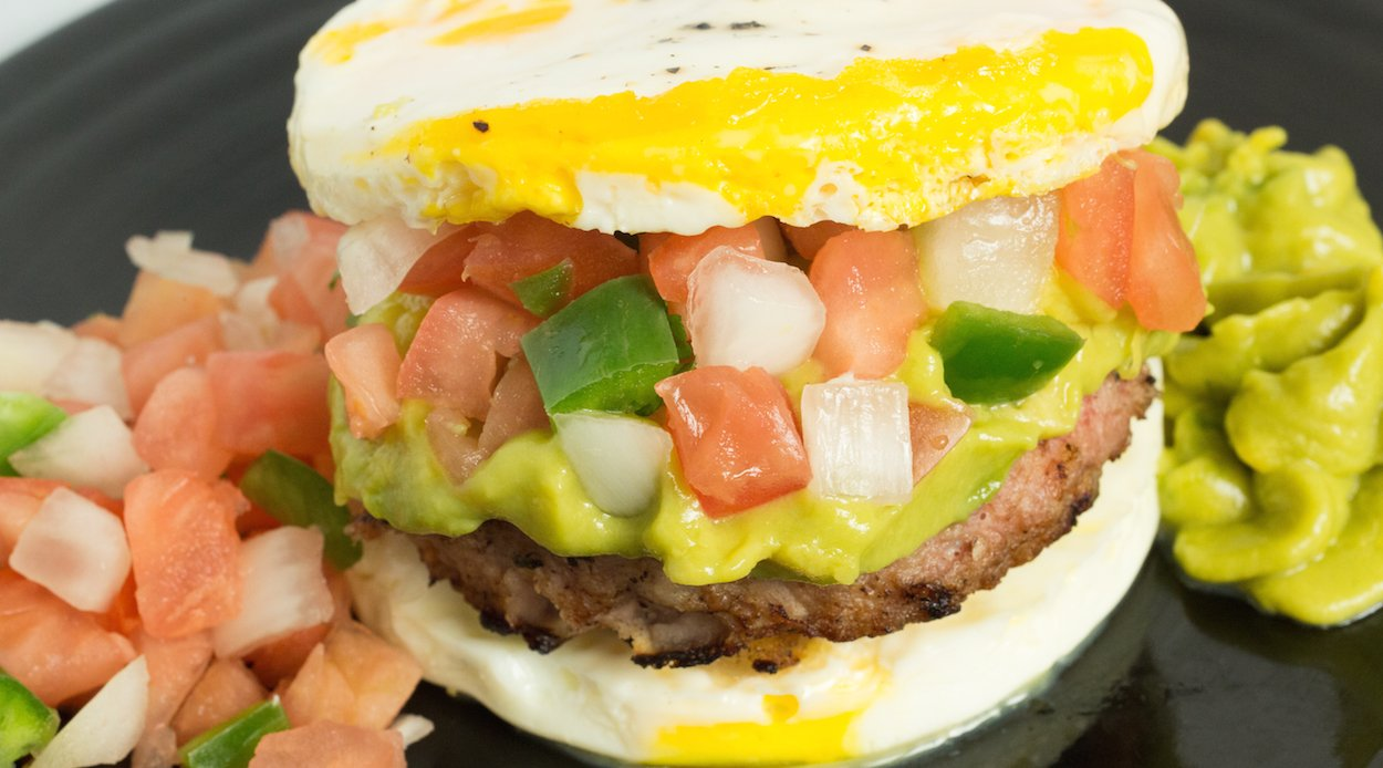 A homemade pork sausage patty sandwiches between two eggs topped with pico de gallo