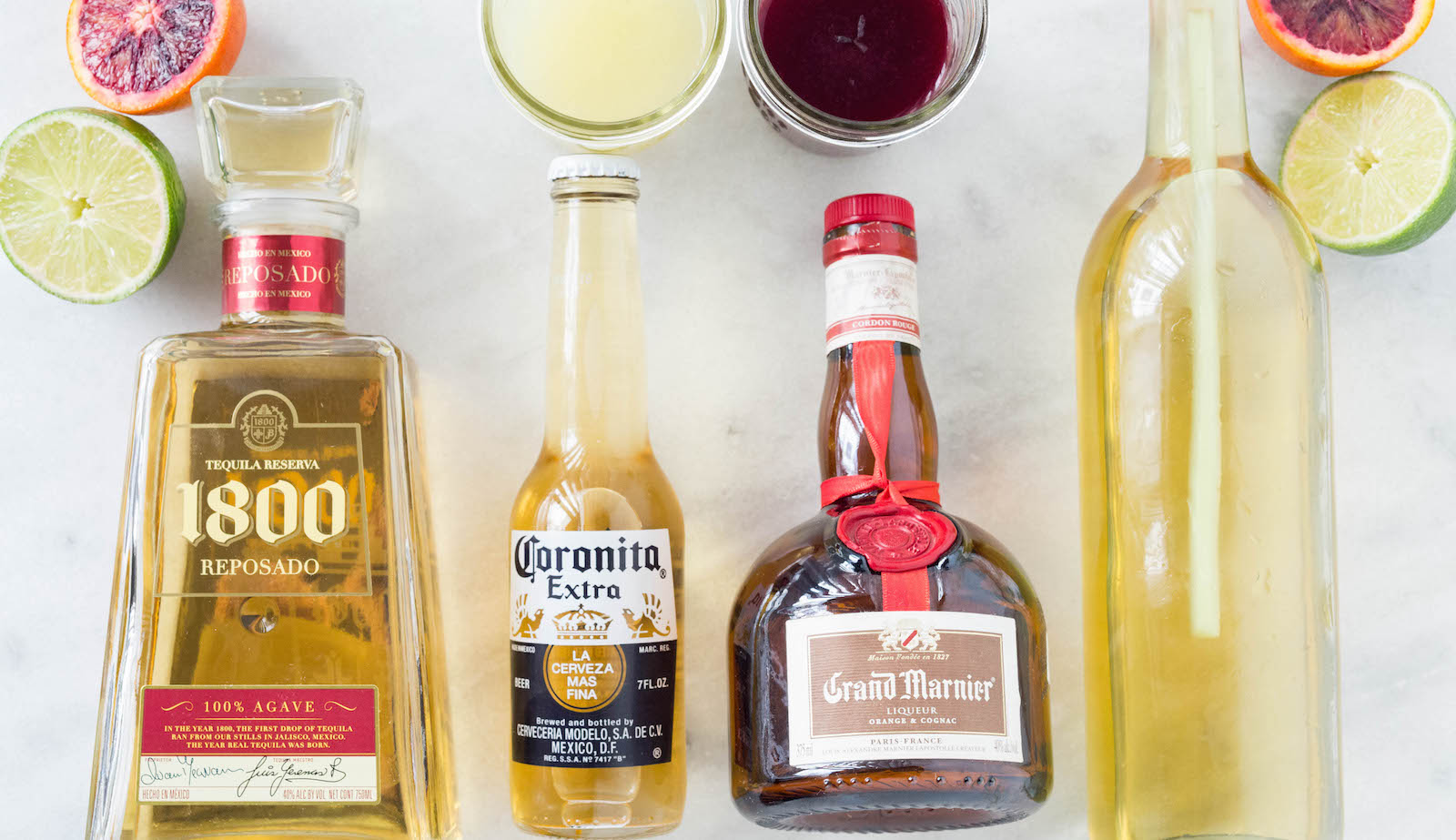 All the ingredients to make our Coronarita (Beer Margarita) Recipe: lemon juice, blood orange juice, lemongrass simple syrup, coronita, tequila, and Grand Marnier.