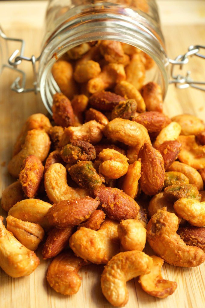 Buffalo spiced nuts spilling out of a glass jar on a cutting board