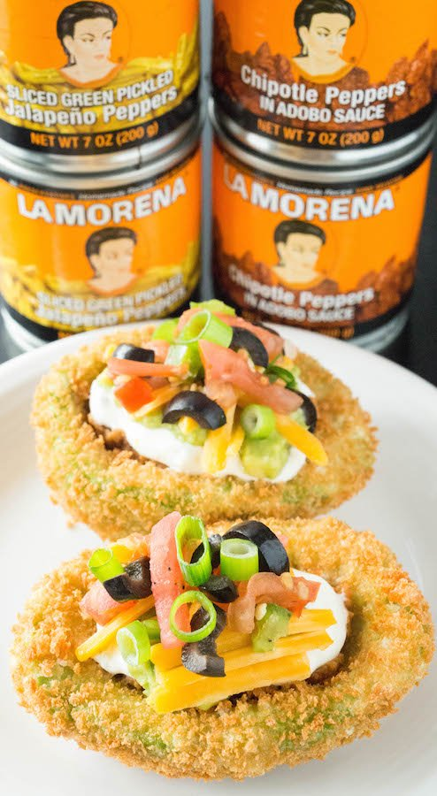 Fried avocados stuffed with spicy seven layer dip. The perfect game day food!