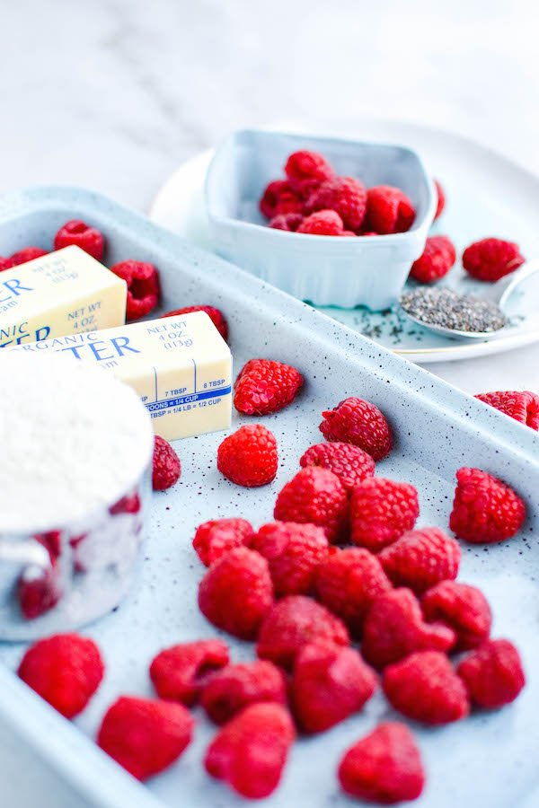 Ingredients for Raspberry Pop-Tarts are displayed. Butter, sugar, and fresh raspberries on a pan.