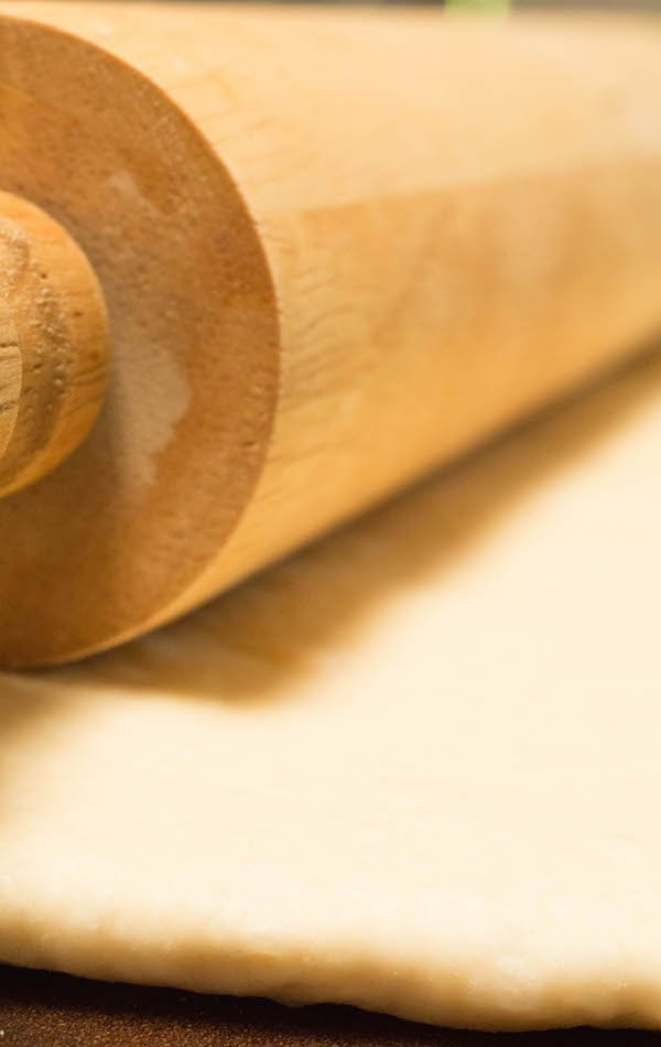 Close up of a wooden rolling pin rolling out pizza dough