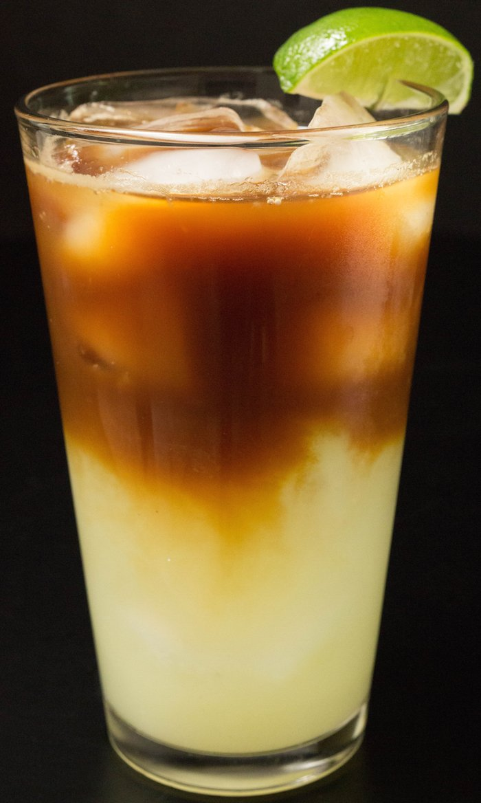 A layered drink in a tall glass with ice and a lime wedge. Green lime juice bottom later and brown coffee top layer.