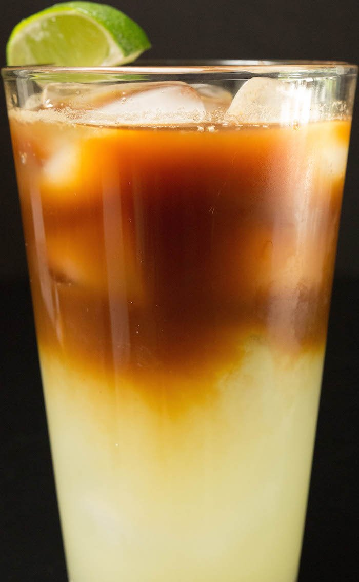 Medium close up of a layered Caipirinha cocktail with espresso on top.