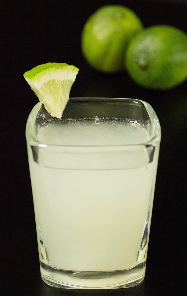 A single lime drop shot in a square glass on a black background with two limes.