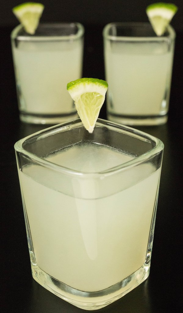 3 lime drop shots in square glasses on a black background