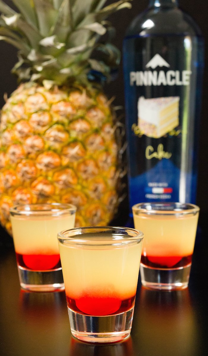Three layered pineapple upside down cake shots in front of a vodka bottle and a pineapple