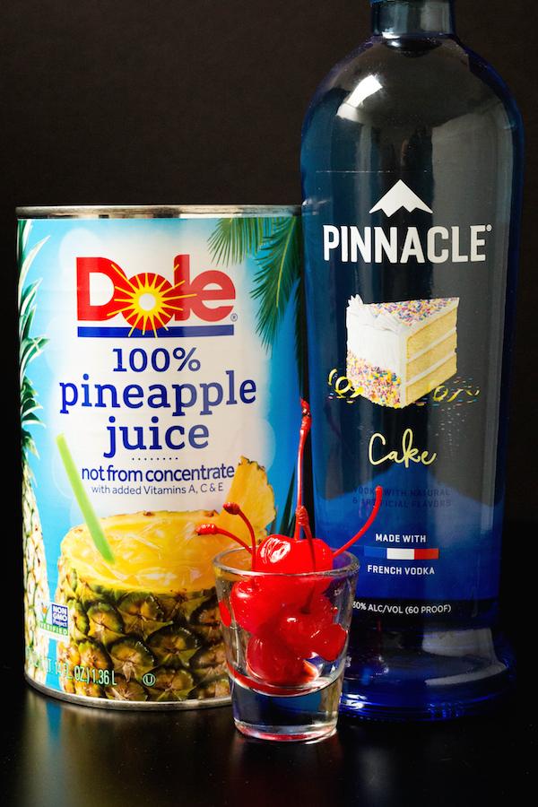 A large can of pineapple juice, a bottle of cake vodka, and a shot of maraschino cherries on a black background
