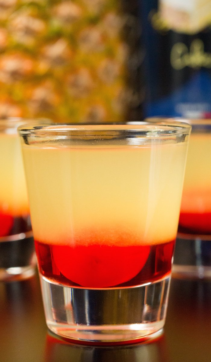 Close up of a layered pineapple upside-down cake shot with a blurred out black background