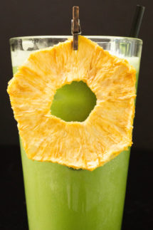 A bright green iced matcha drink garnished with a dried pineapple ring in a tall glass on a black background
