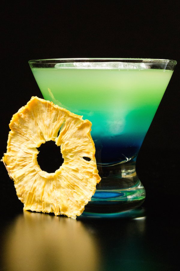 A layered blue to green Quarantiki cocktail in a glass on a blackbackground.