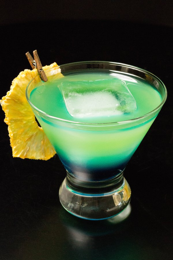 A blue to green layered cocktail garnished with a pineapple slice in a glass on a black background.