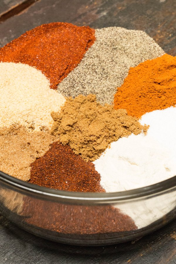 Multi-colored spices for BBQ spice rub arranged in piles in a large glass bowl