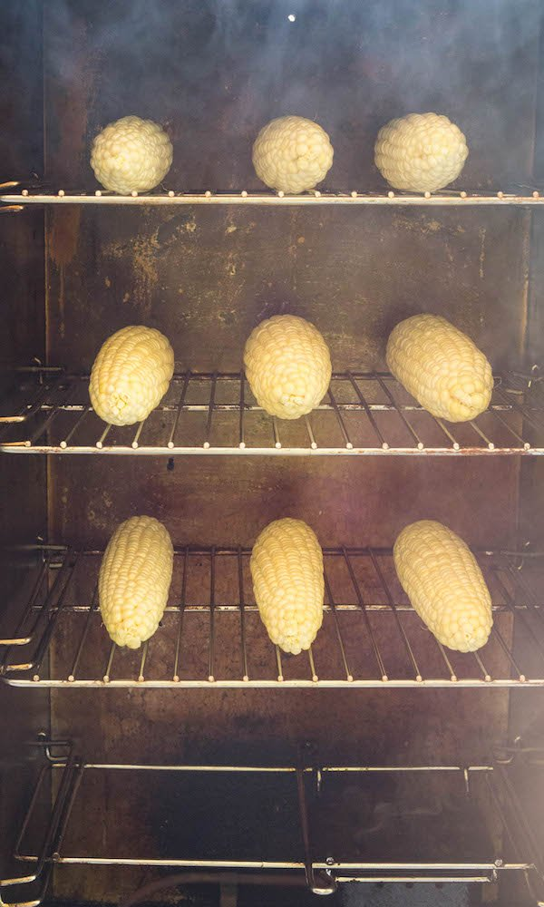 Head-on view of three racks of corn on the cob being cooked in a smoker