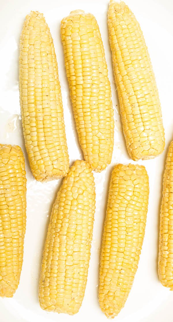 Overhead shot of seven smoked corn on the cobs on a white background