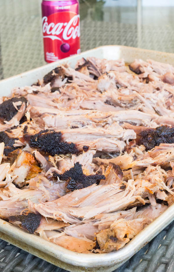 Wide shot of cherry coke smoked pulled pork on a metal baking sheet.