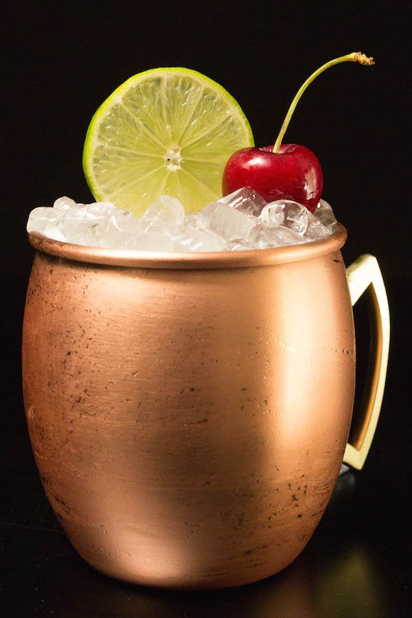 A copper mug filled with cherry lime moscow mule cocktail sits on a black background