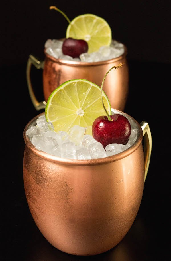 Two cherry limeade moscow mules in copper mugs on a black background