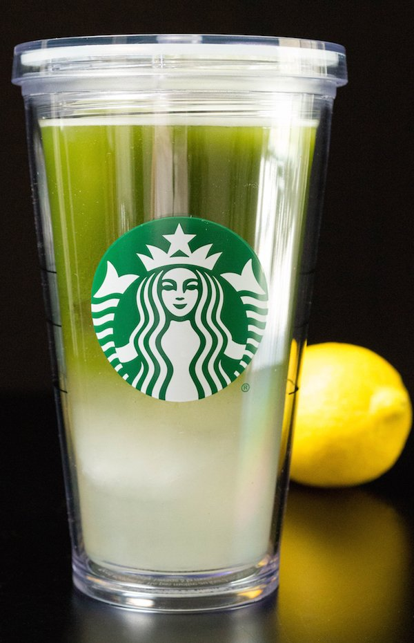 A grande starbucks cup filled with matcha lemonade. A lemon sits in the background.