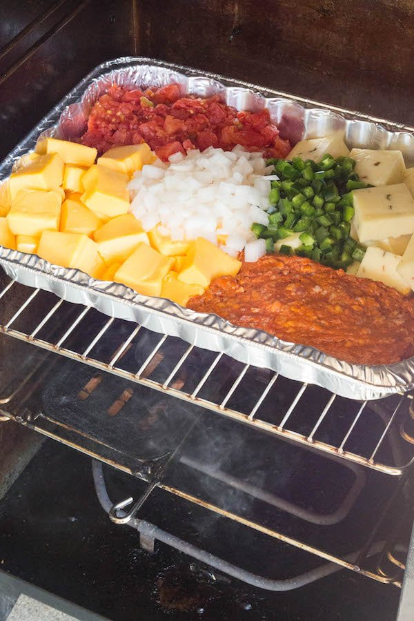 A pan of smoked queso ingredients inside an electric smoker