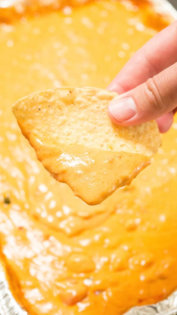 Close up of a finger holding a tortilla chip that has been dipped in smoked queso