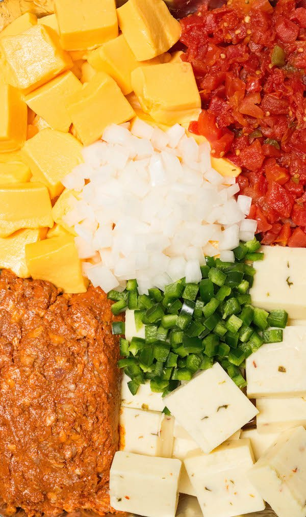 Close up of smoked queso ingredients: velveeta, pepper jack, chorizo, rotel, chopped white onion, and chopped jalapenos