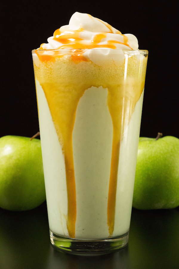 A glass of disney's caramel apple smoothie on a balck background with two green apples by it's side