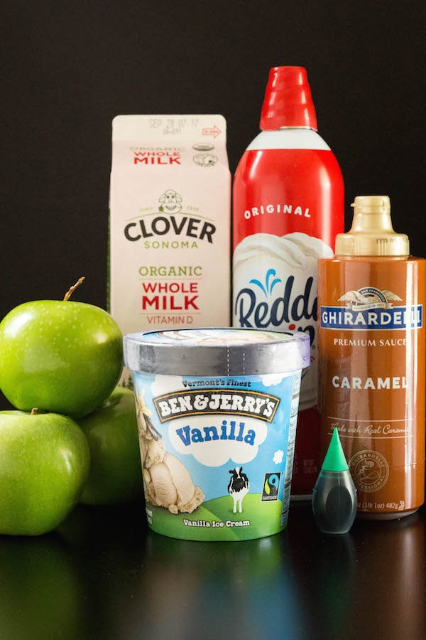 A carton of whole milk, 3 green apples, ice cream, whipped cream, and caramel on a black background