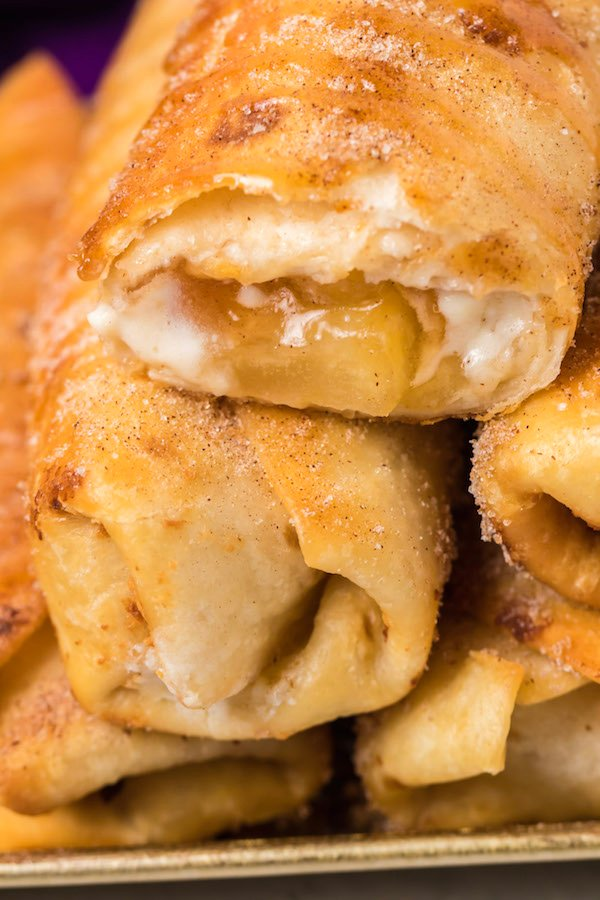 Close up of a stack of caramel apple cheesecake chimichangas. The on top is cut open to reveal the apple cheesecake filling inside.