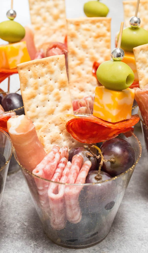 A plastic punch cup filled with meats, cheese, and grapes.